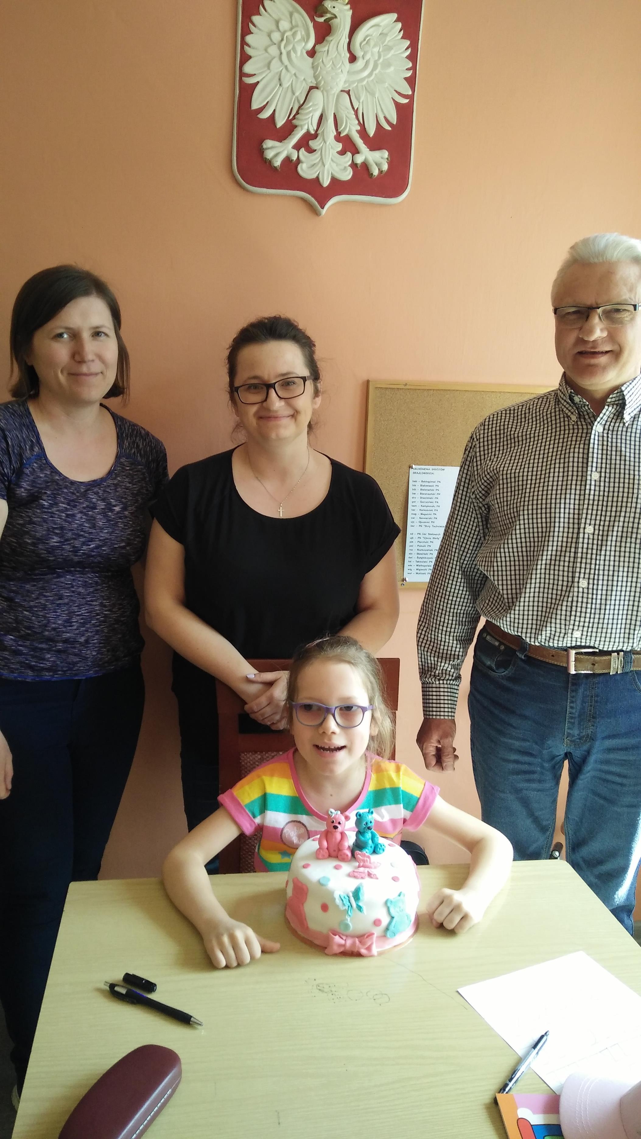 Hania z tortem za nią jej mama, gosia i dyrektor